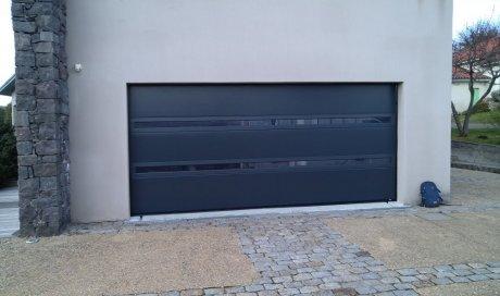 Remplacement d'une porte de garage sectionnelle avec hublot panoramique de la marque Flip (La toulousaine) motorisée Somfy io enAluminium à Orcines (63870).